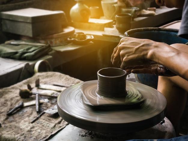 Le mani di potter modellano l'argilla morbida per creare un vaso di terracotta