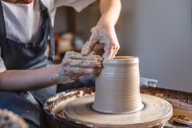 Potter lavora su una ruota di potter facendo un vaso