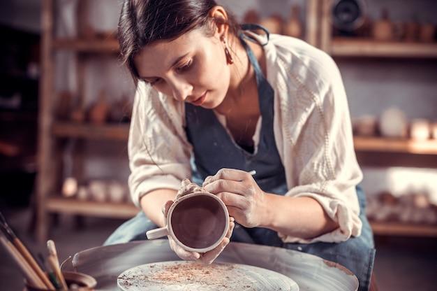 Il vasaio lavora in officina. mani e un primo piano del tornio da vasaio.
