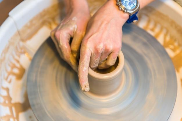 Pottering: creazione di una tazza di argilla in corso. girato con un piccolo grip