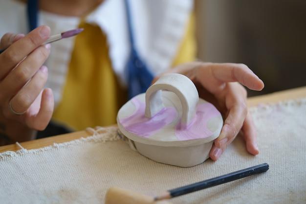Processo creativo di creazione di ceramiche nello studio del vasaio con stoviglie di argilla di pittura di ceramista femminile