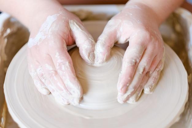 Hobby artigianale di ceramica. mani che formano e modellano una palla di argilla sul tornio del vasaio
