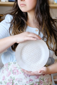Abilità artigianali della ceramica. l'arte tradizionale della creazione della ceramica. vasaio che tiene piatto di argilla. concetto di stoviglie artigianali