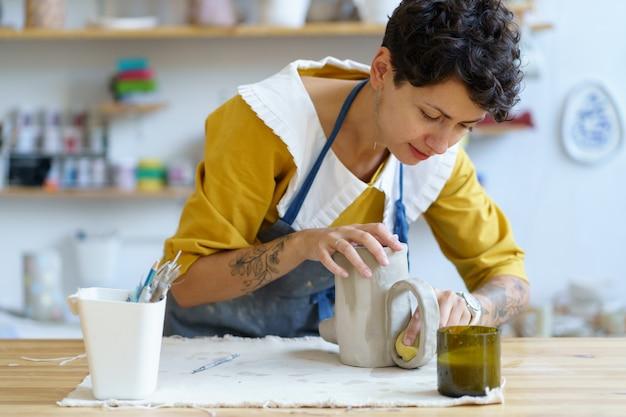 Hobby di ceramica o fabbricazione di ceramica piccola impresa giovane artista brocca di stampaggio di argilla grezza in studio