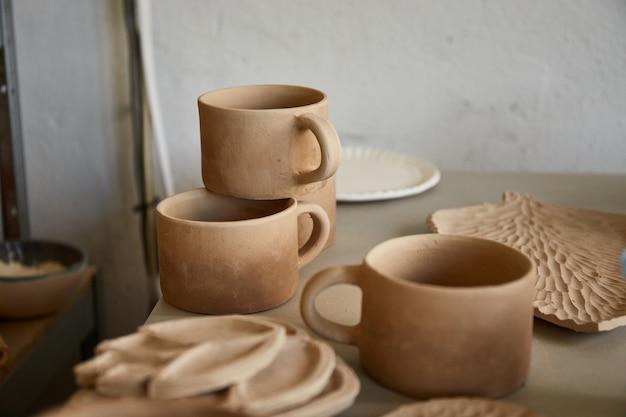 Studio di ceramica il processo di creazione della ceramica. la maestra ceramista lavora nel suo studio. posto di lavoro di vasaio