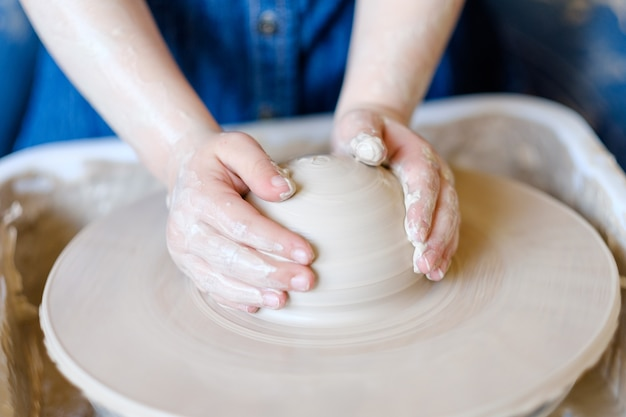 Laboratorio di ceramica. artigianato fatto a mano. artigiano bambino che lavora con l'argilla sulla tornitura del tornio da vasaio.