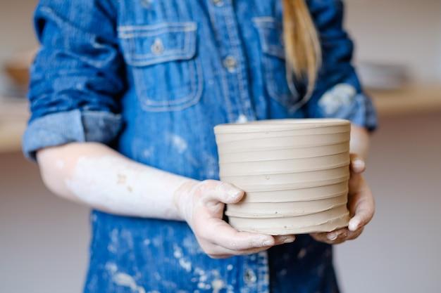 Laboratorio di ceramica. giovane mano artigiana che mostra una brocca di argilla artigianale. concetto di stoviglie fatte a mano