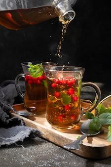 Versare il tè nero da una teiera trasparente in una tazza su fondo nero.