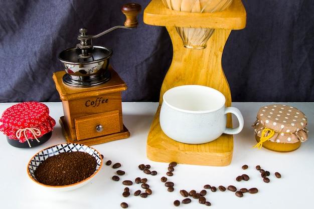 Versare sopra la caffettiera, la tazza di caffè e la tazza, riprese in studio