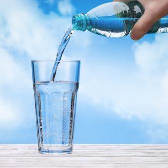 Versare l'acqua frizzante dalla bottiglia di plastica in un bicchiere grande. bottiglia in mano dell'uomo. cielo con nuvole.
