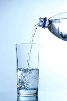 Versare l'acqua dalla bottiglia nel bicchiere, sulla superficie azzurra