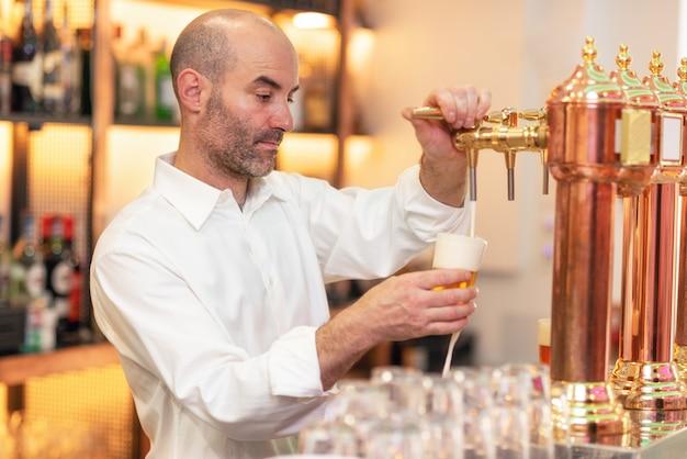 Versare la birra per il cliente. barista versando birra stando in piedi al bancone del bar.