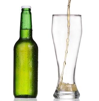Birra di versamento dalla bottiglia isolata su fondo bianco