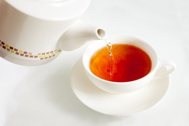Versare acqua bollente in una tazza da tè dal bollitore bianco