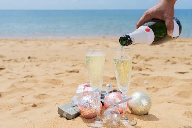 Versare champagne in bicchieri con confezione regalo di natale e decorazioni sulla spiaggia in riva al mare tropicale
