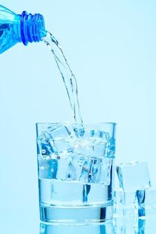 Versando acqua potabile pulita dalla bottiglia di plastica blu in vetro su sfondo blu
