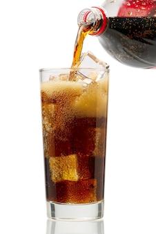 Versare la cola nel bicchiere con cubetti di ghiaccio