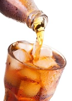 Cola di versamento in vetro con ghiaccio dalla bottiglia isolata su priorità bassa bianca