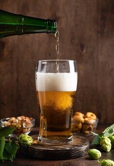 Versamento di birra fredda in vetro con schiuma birra e snack sul tavolo di legno scuro