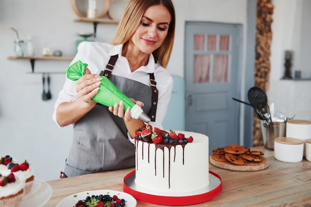 Crema da versare. la donna sta al chiuso in cucina con torta fatta in casa.