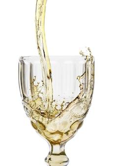 Versare la bevanda nel bicchiere di vino di cristallo isolato su bianco