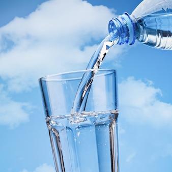 Versando acqua potabile dalla bottiglia di plastica in vetro, contro il cielo blu con nuvole. copia spazio.