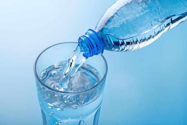 Versare l'acqua potabile dalla bottiglia di plastica in vetro, vista dall'alto. acqua frizzante con bollicine in bicchiere grande. copia spazio.