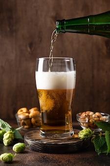 Versare birra fresca dalla bottiglia nel bicchiere da birra prodotto di qualità preparato e artigianale