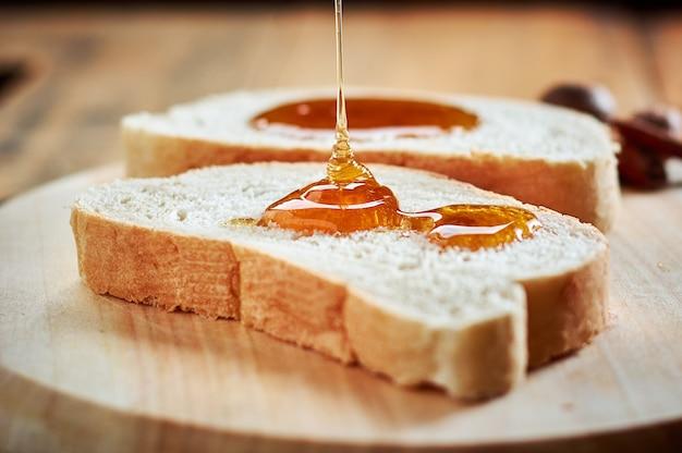 Versando miele fresco su fette di pane con un cucchiaio di legno
