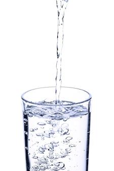 Versamento di acqua fresca in vetro su sfondo bianco