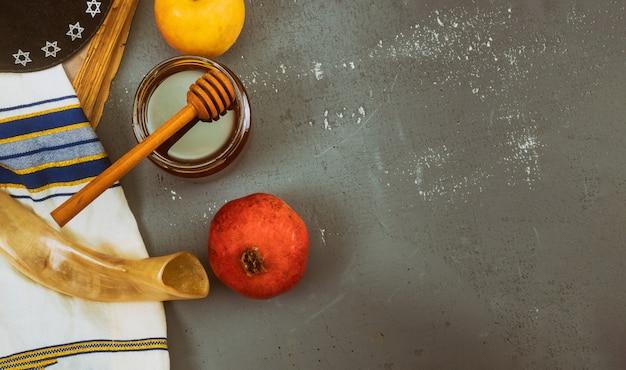 Versare miele su mela e melograno con simboli di miele del capodanno ebraico, rosh hashanah.