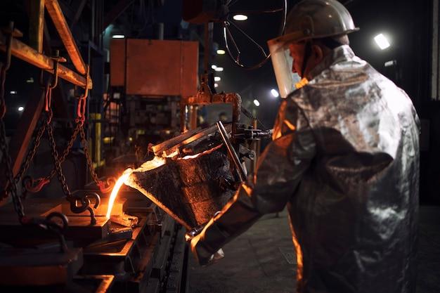 Colata di ferro caldo in fonderia, produzione di acciaio industriale e fusione.