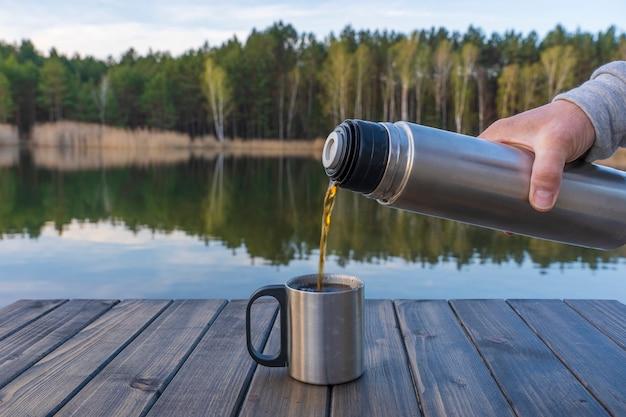 Versare il tè caldo in una tazza da un thermos al mattino vicino al lago e alla foresta in primavera, primo piano. natura e concetto di viaggio