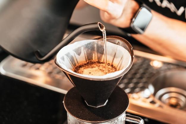 Versando acqua calda per gocciolare il caffè arabica