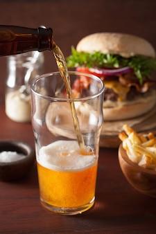 Versare la birra chiara india in vetro pinta e fast food