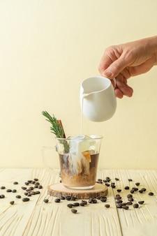 Versando il latte nel bicchiere di caffè nero con cubetto di ghiaccio, cannella e rosmarino su fondo di legno wood