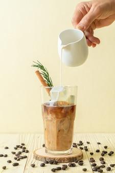 Versando il latte in un bicchiere di caffè nero con cubetto di ghiaccio, cannella e rosmarino su fondo di legno