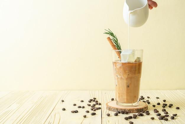 Versando il latte nel bicchiere di caffè nero con cubetto di ghiaccio, cannella e rosmarino su fondo di legno