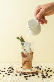 Versando il latte nel bicchiere di caffè nero con cubetto di ghiaccio, cannella e rosmarino sulla fetta di legno
