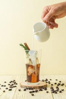 Versando il latte nel bicchiere di caffè nero con cubetto di ghiaccio, cannella e rosmarino sulla superficie del legno