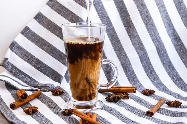Versare il latte nel bicchiere con caffè freddo sul tavolo grigio con bastoncini di cannella e stelle di anice