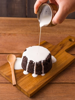 Versando la salsa di latte sui brownie al cioccolato sul piatto di legno e sullo sfondo di legno. prodotti da forno e dolci fatti in casa