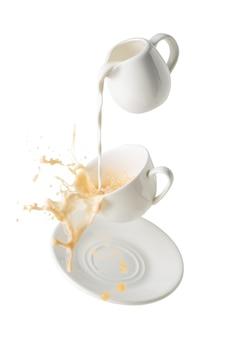 Versare il latte e schizzi di tè al latte dalla tazza volante e piattino isolato su priorità bassa bianca