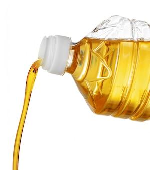 Olio di versamento per la cottura in una bottiglia isolata su bianco.