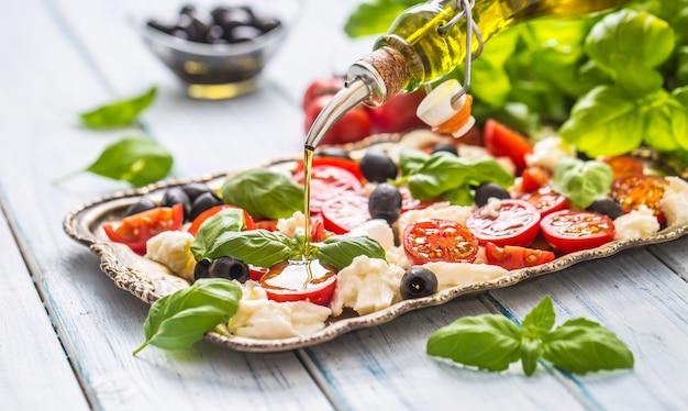 Versare l'olio d'oliva su insalata caprese. pasto sano italiano o mediterraneo