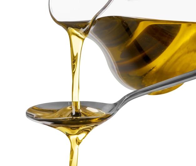 Versando l'olio d'oliva dalla brocca di vetro nel cucchiaio su priorità bassa bianca