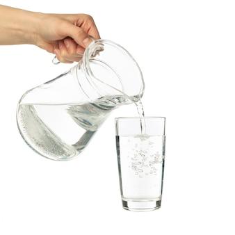 Acqua dolce purificata di versamento dalla brocca in vetro, isolata su bianco