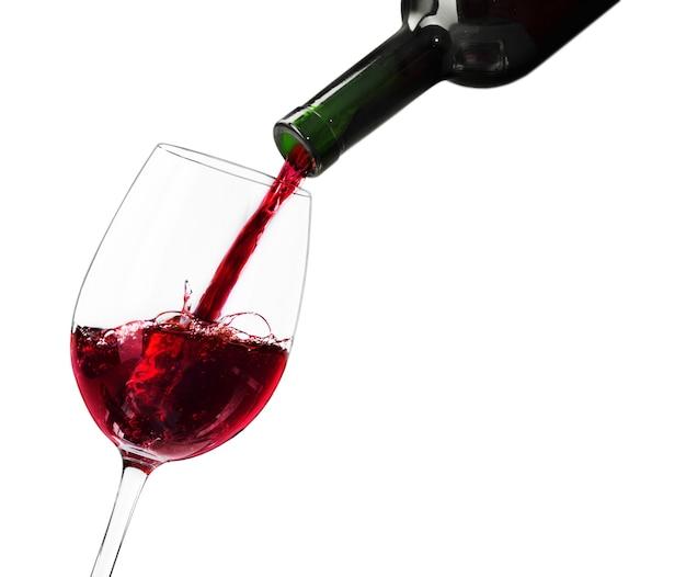 Versare il vino rosso in un bicchiere su sfondo n