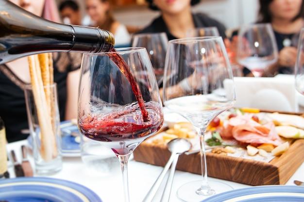 Versare il vino rosso in un bicchiere nel ristorante con antipasti