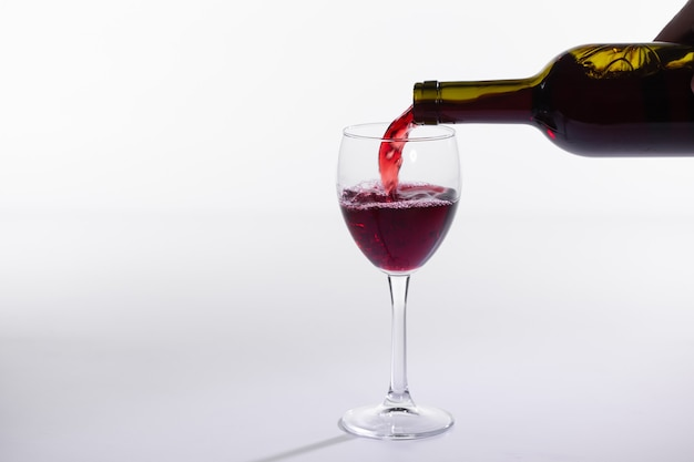 Versare il vino rosso nel bicchiere su sfondo bianco con copia spazio